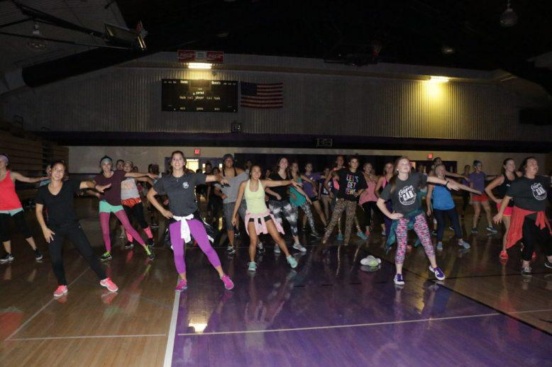 A group of students doing Zumba in a campus gym