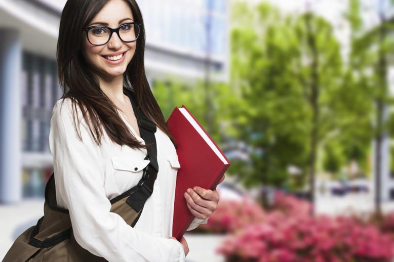 Confident woman holds textbook with backpack slung across her