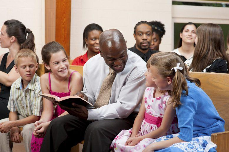 A man reading the Bible to a group of children