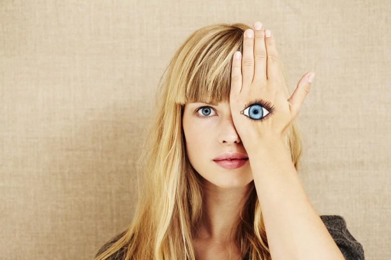 Woman covering her left eye with a painting of an eye on her hand