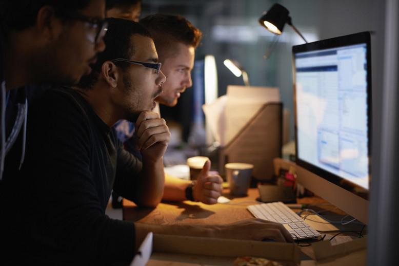 three men looking at a computer