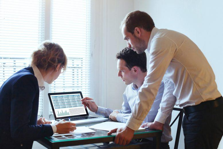 Male business analyst points out something on screen to two other professionals