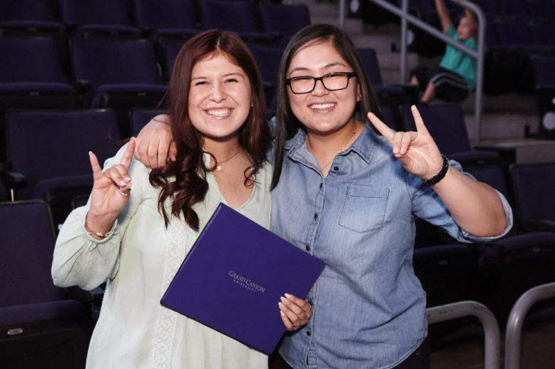 two students holding a lopes up