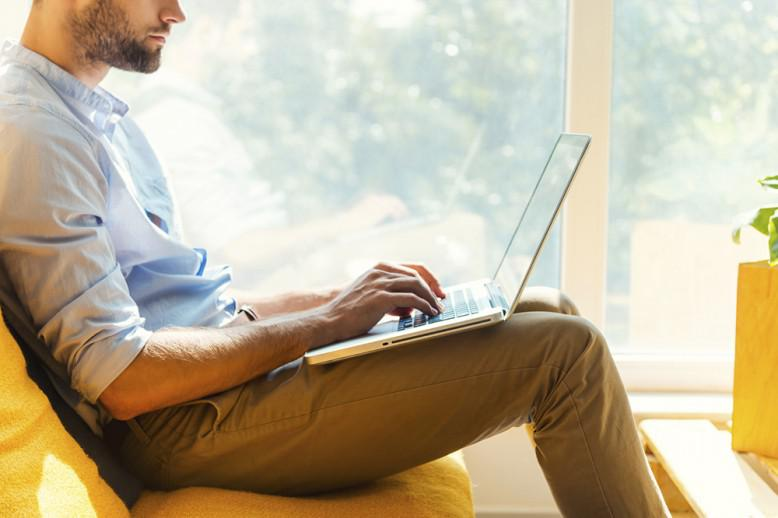 Adult man sits while working on laptop