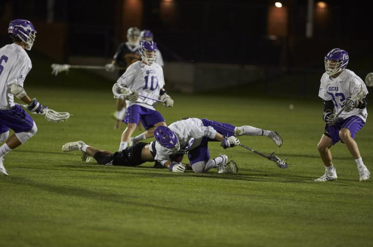 GCU lacrosse players in mid-play on the field