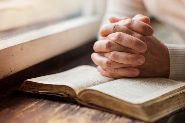 Hands clasped in praying position over open bible next to windowsill