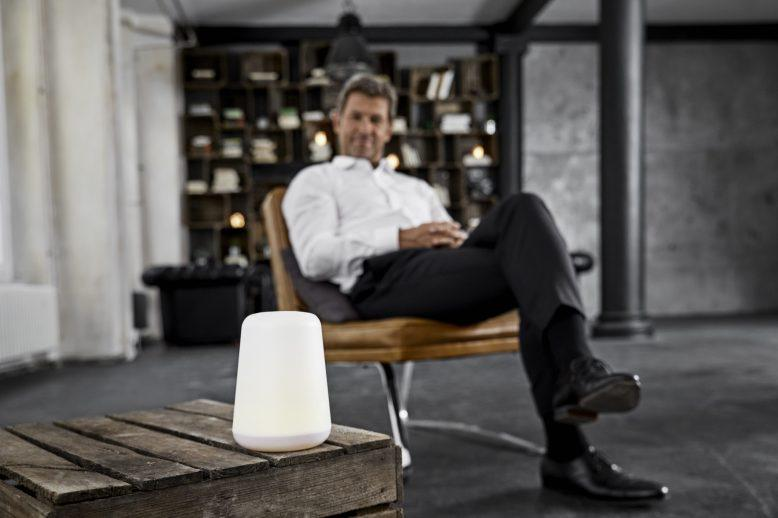 Man sitting beside a digital assistant