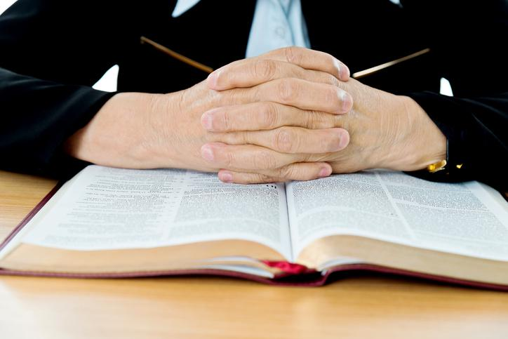 A pair of hands folded over the Bible