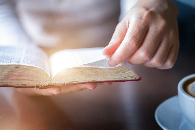 Hand turning a page in the bible