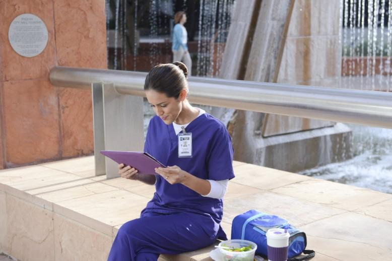 nursing student looking at a clipboard