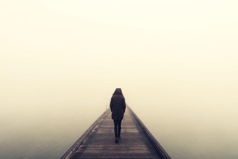 A man walking alone on a foggy bridge