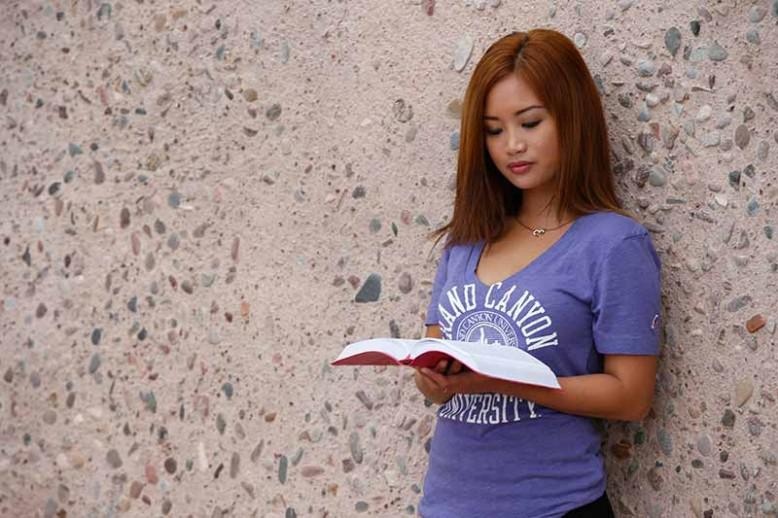 Woman reading a book against a stone wall