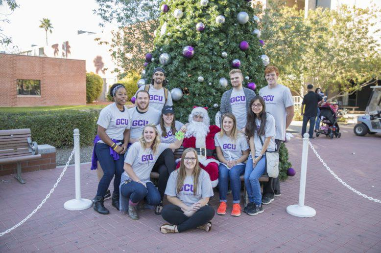 GCU students in front of a Christmas tree on campus