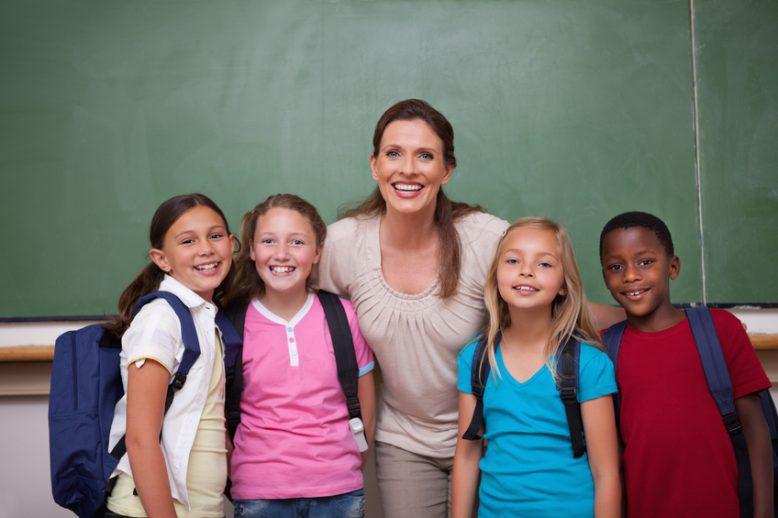 Elementary teacher hugging her students