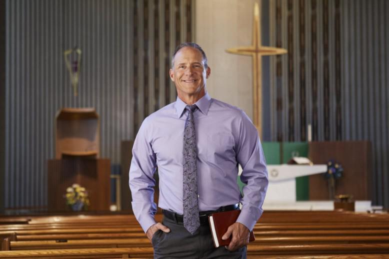 A man in a purple shirt standing in a church