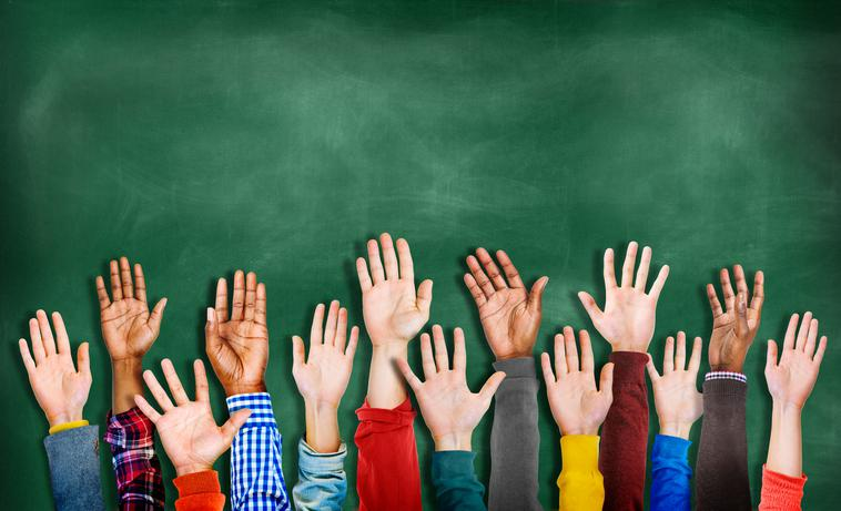 group of children raising hands in front of chalkboard
