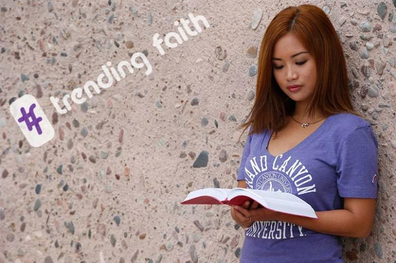 Female student in purple v-neck GCU shirt reads the Bible
