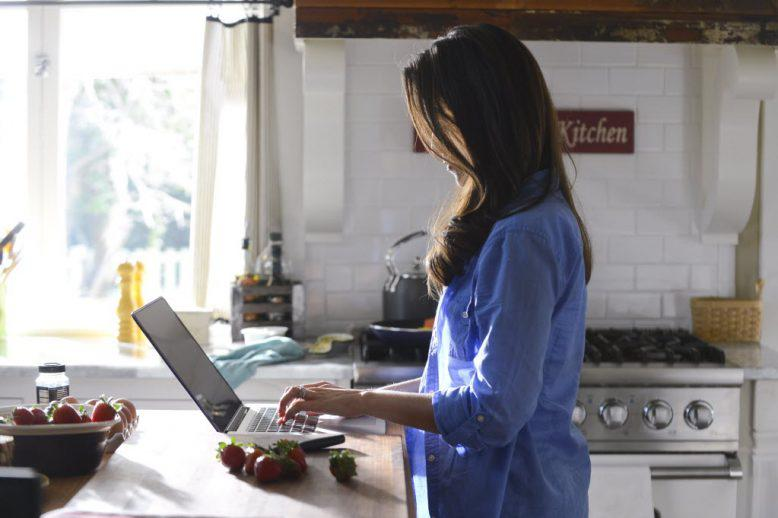 a woman in her kitchen looking up information
