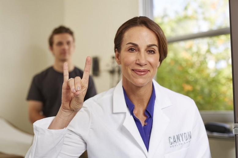 GCU nurse holding her hand in a lopes up