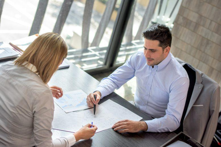 Financial analyst shows details to another professional