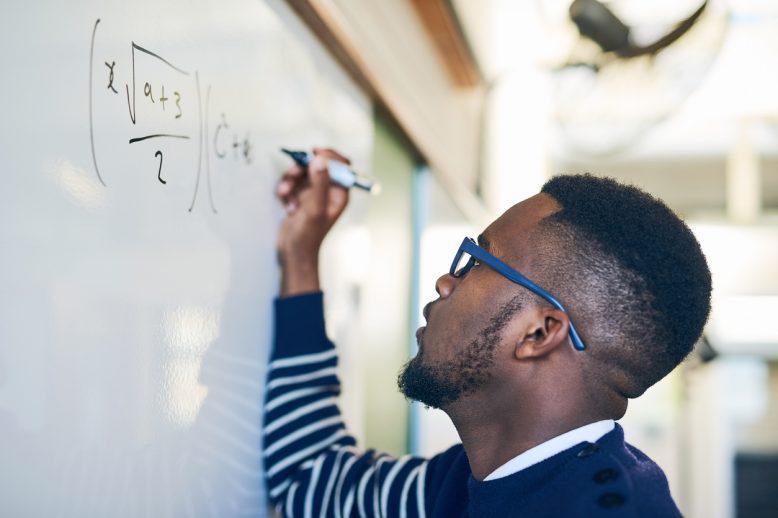 Man writing math on the board