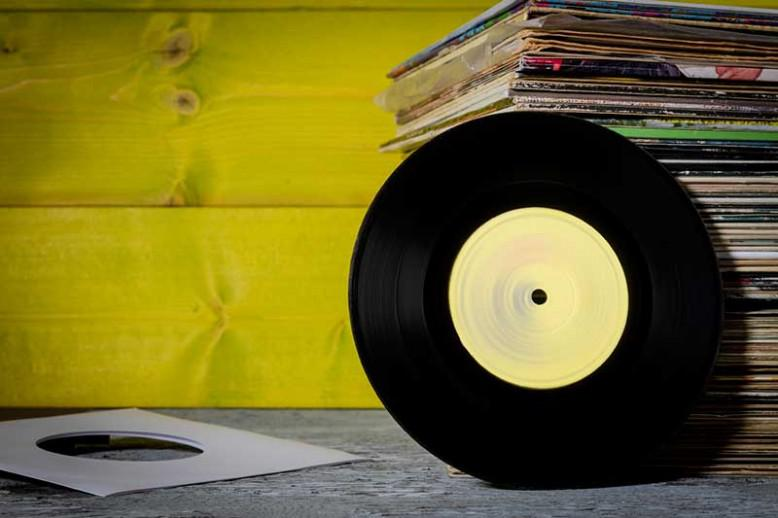Vinyl record leans against stack of vinyl record sleeves with yellow wood background