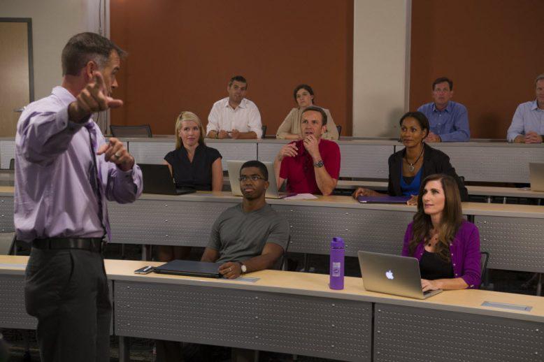 Adult students listen to an evening class professor