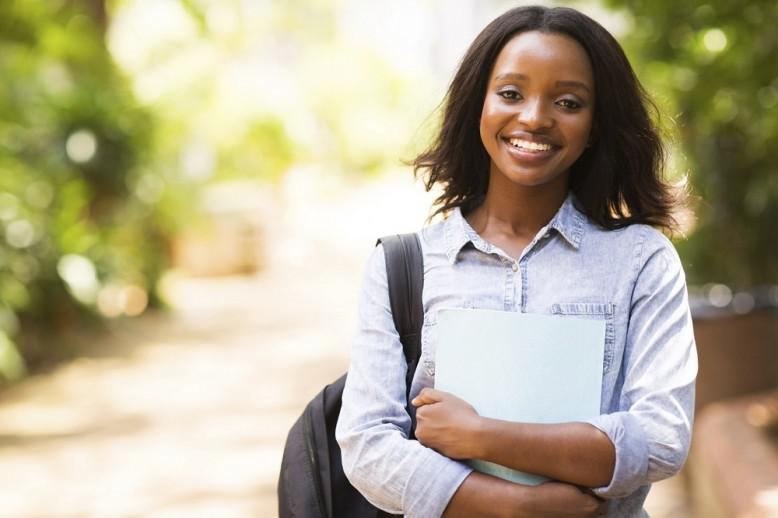 girl wearing backpack and holding notebook