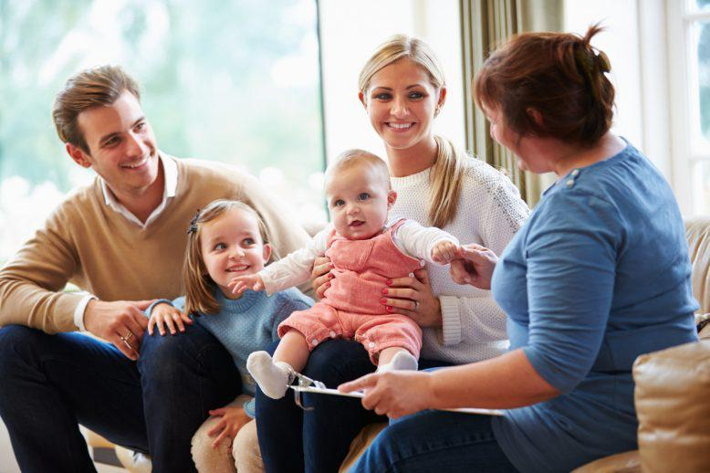 Social worker visits smiling family of four with two younger girls