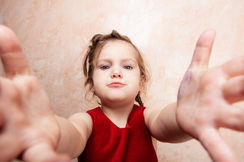 Young child reaching her arms out