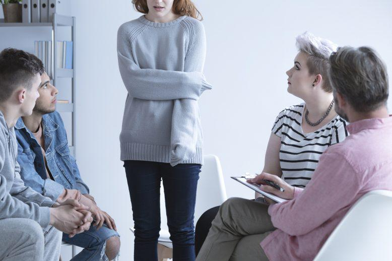 Girl holding her arm in a group counseling setting
