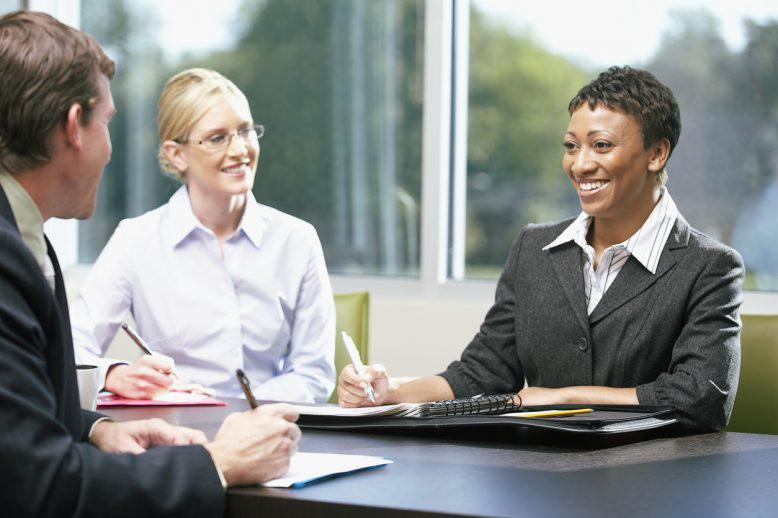 Trio of HR managers take notes in a conference room meeting