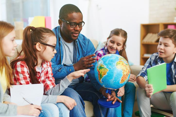 teacher holding globe and surrounded by young students