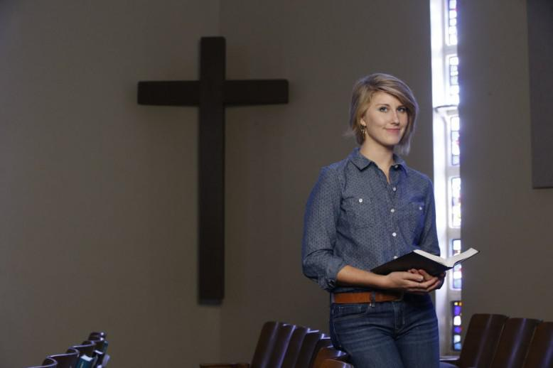 woman standing in front of cross