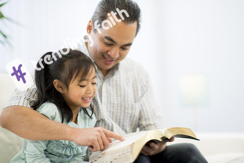A man reading the Bible to his daughter with the Trending Faith logo