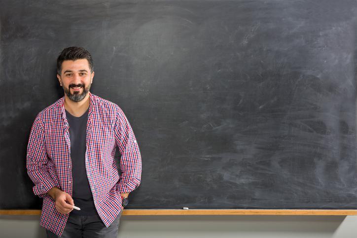 teacher standing next to chalkboard