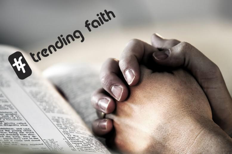 Hands clasped in prayer position on top of open bible with hashtag trending faith text on top