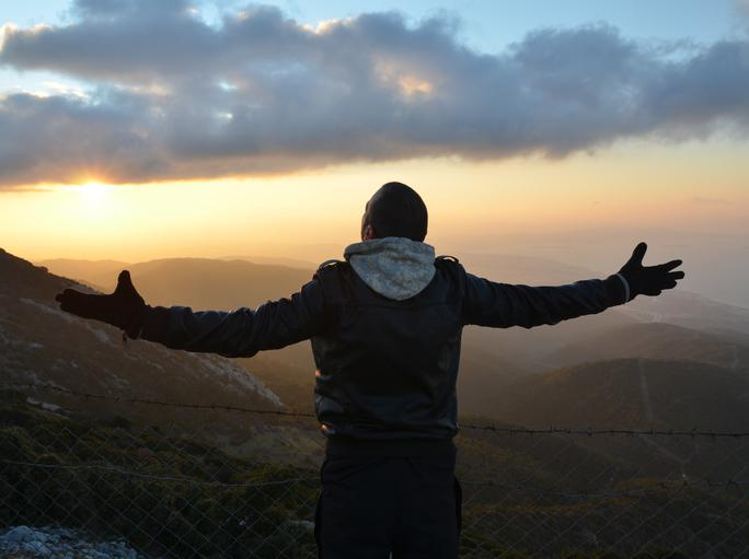 A man spreading his arms at the top of a mountain at sunset