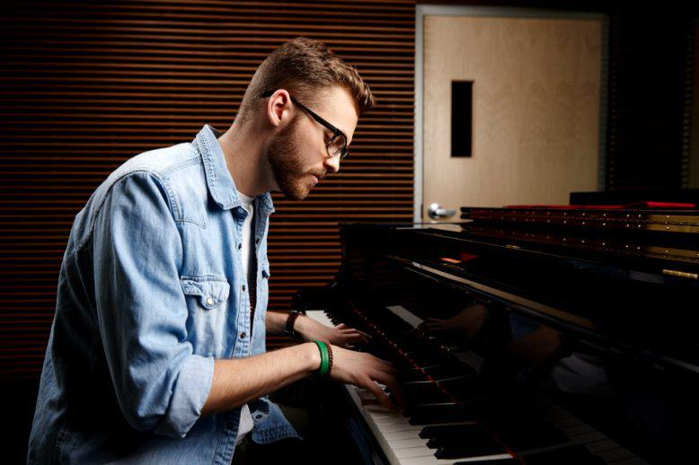 A man playing worship music on the piano