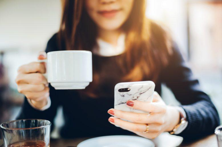A person on their phone with coffee