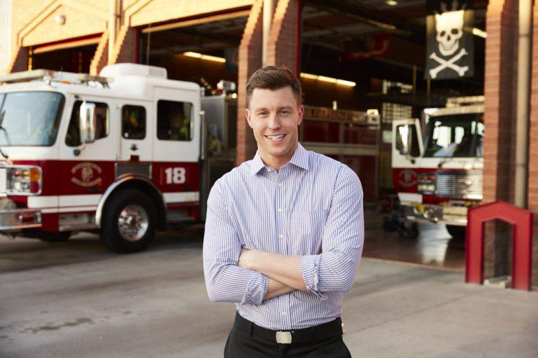 Businessman stands outside fire station