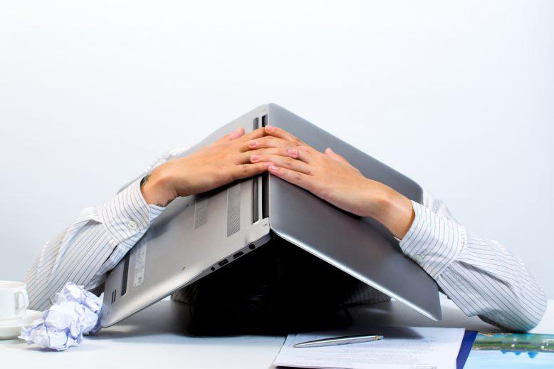 Entrepreneur handling failure poorly with a laptop over his head