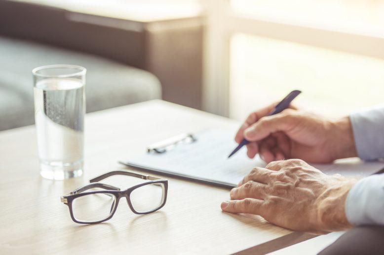 Glass of water and pair of eye glasses on desk while an older male uses checklist
