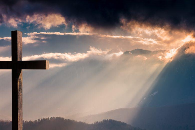 A cross facing golden sun-rays