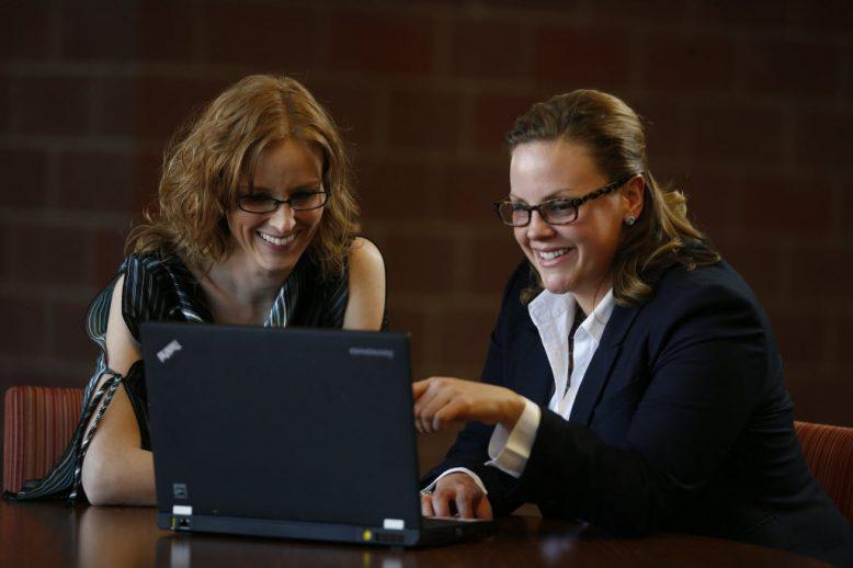 Two professional woman smile while analyzing data on a laptop