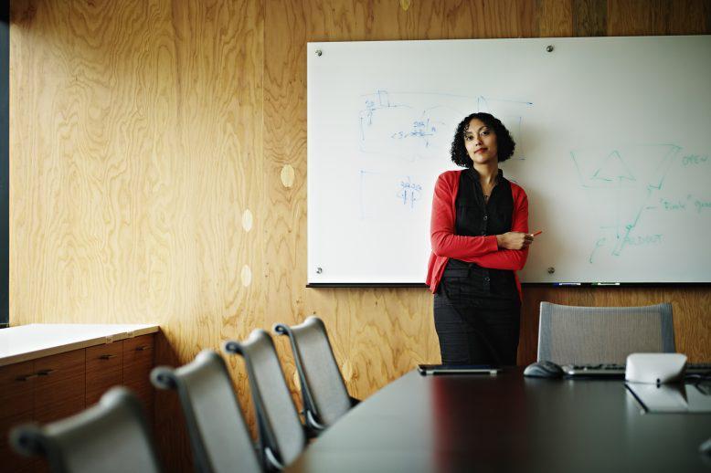 teacher leaning against a board