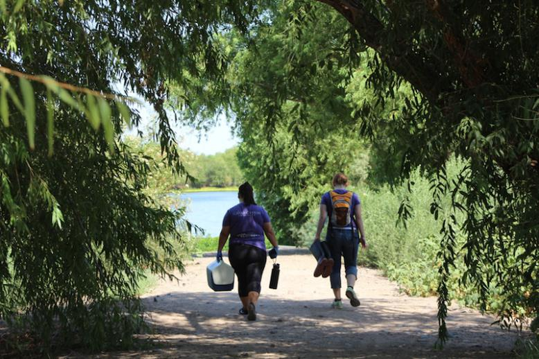 Two people walk up to a lake with equipment in their hands