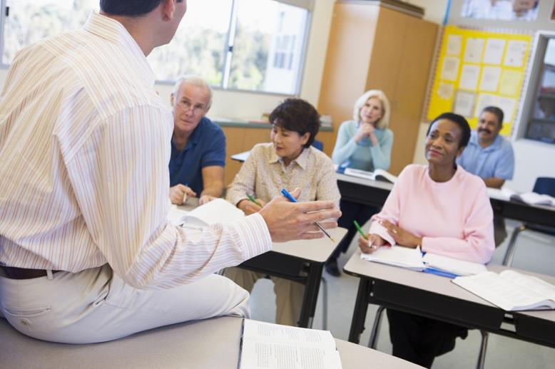 Male teacher sits on desk facing his class of adult students