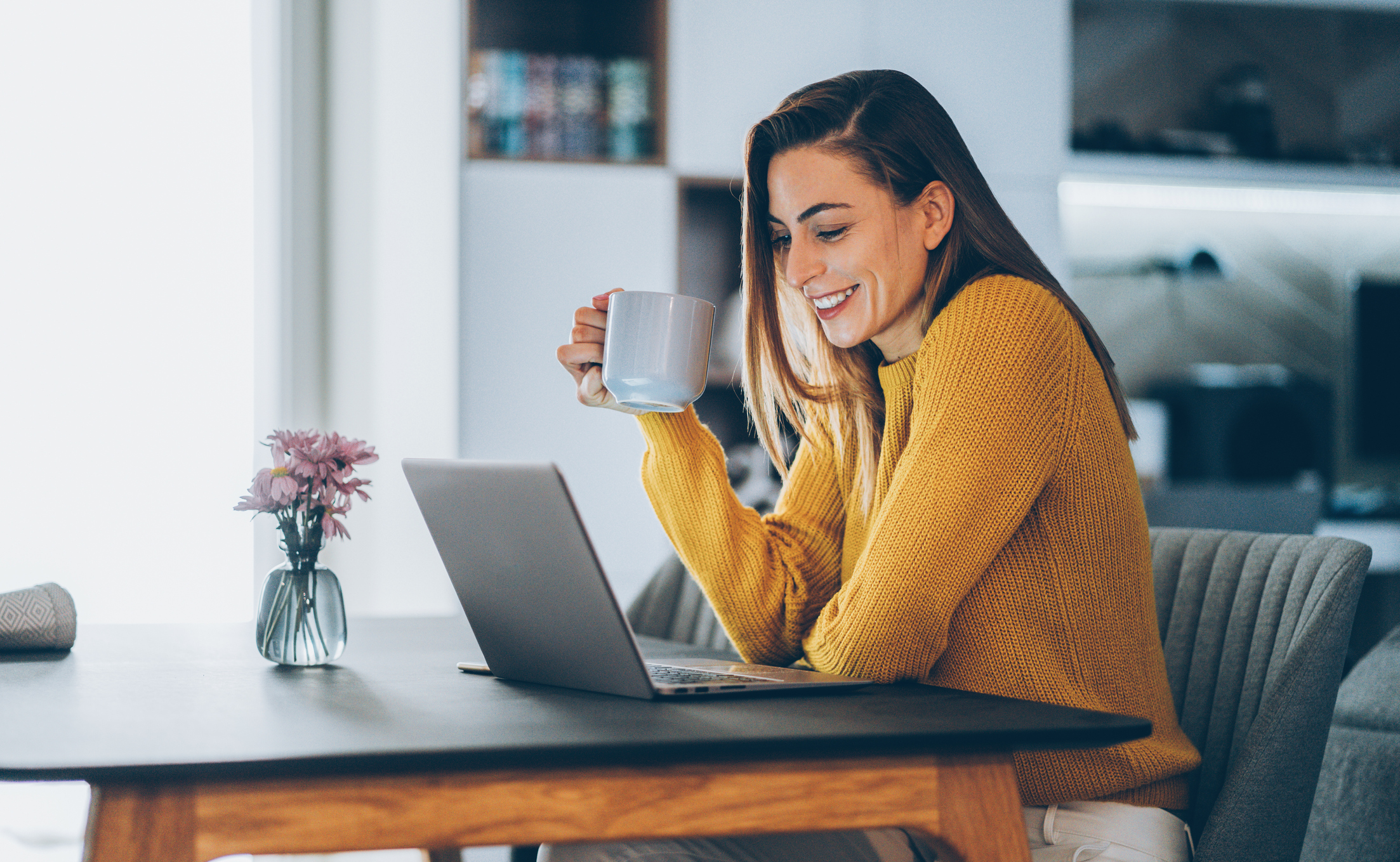 girl holding coffee cup and looking at computer