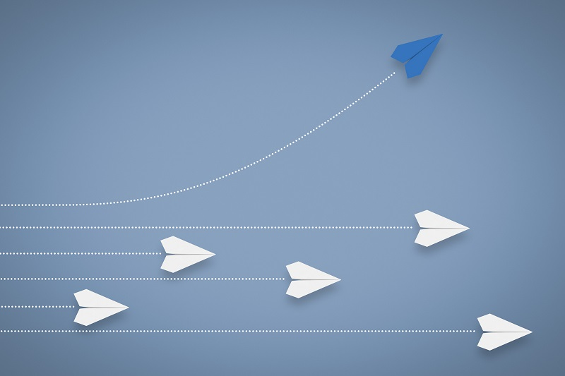 A Paper airplane changing direction from other paper airplanes